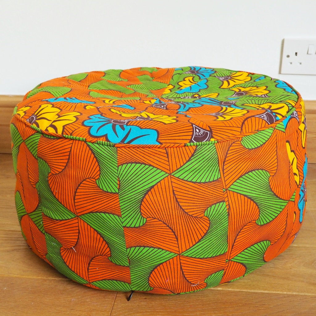 An orange and green pouf made from ankara fabric