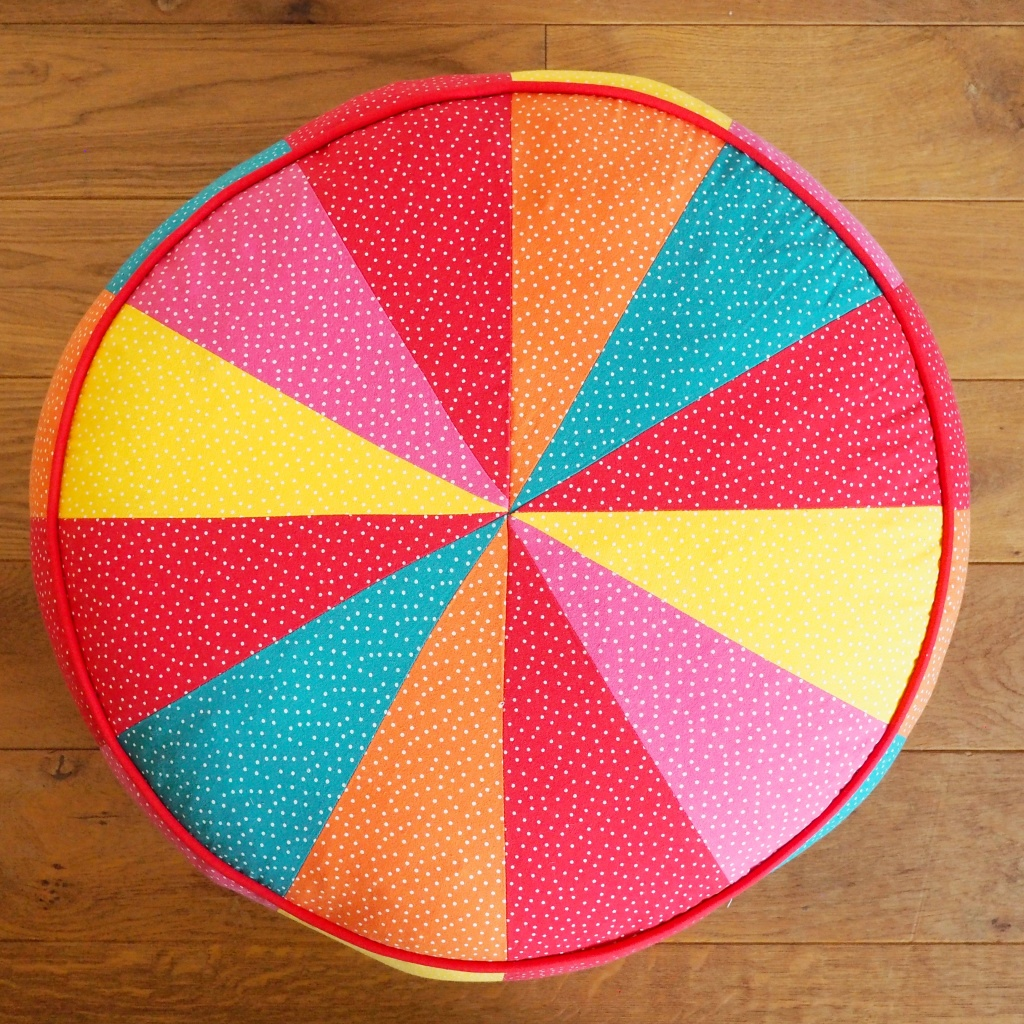 A rainbow coloured pouf, top down view